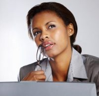 Contemplative young businesswoman holding a spectacles while using laptop